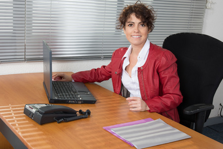 outgoings: A Smiling business woman in red, sitting satisfied at desk Stock Photo