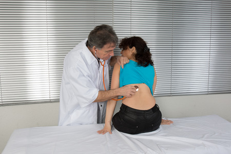 auscultate: male Doctor examining a patient in his medical room