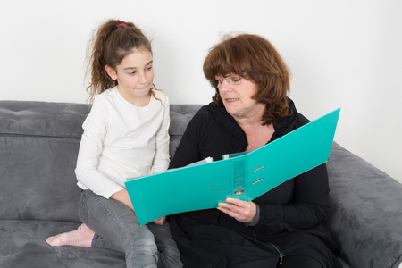 sitter: A woman doing homeworks grandmother to granddaughter sweet young