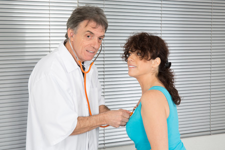 male Doctor examining a patient in his medical room