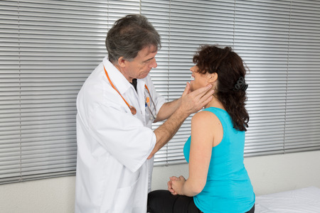 Throat specialist testing lymph nodes of his patient