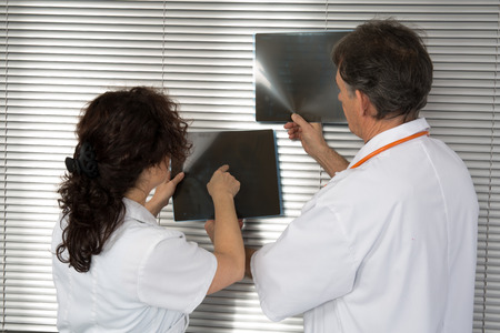 Doctors pointing at his patient x-ray photo
