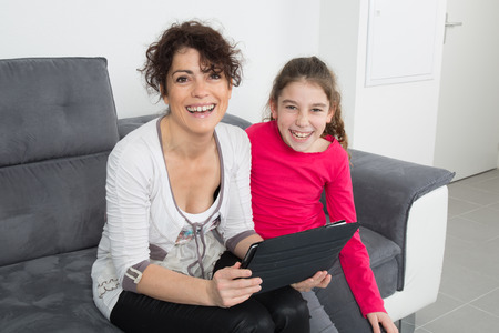 family tickle: bright picture of hugging mother and daughter looking at tablet