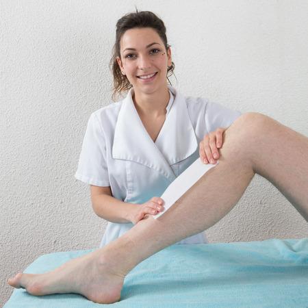 depilacion con cera: Una esteticista pierna cera aplicando banda de cera de un hombre