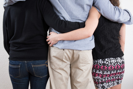 only 3 people: Back view of three people one man and two women looking. Stock Photo