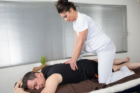 recovery position: Man and woman performing back shiatsu massage Stock Photo