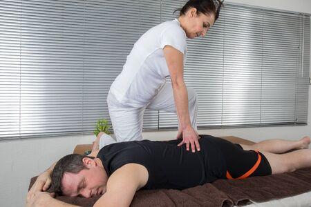 shiatsu: Man and woman performing back shiatsu massage Stock Photo