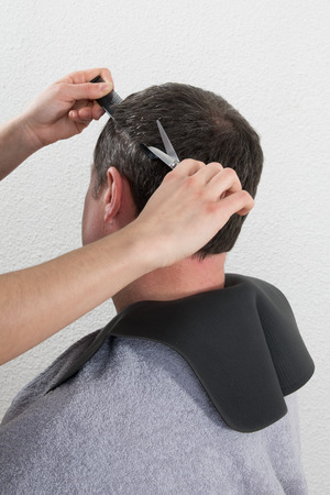 trimming: Hairdresser trimming mans brown hair with scissors Stock Photo
