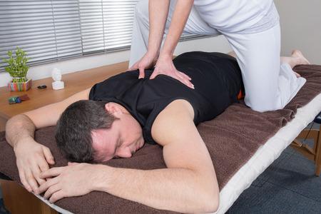 recovery position: Man and woman performing back shiatsu massage Stock Photo