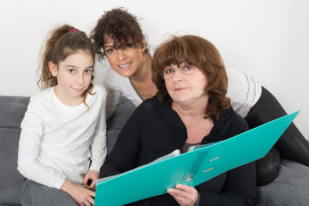 5 10 year old girl: A cheerful grandmother with her daughter and her granddaughter Indoors Stock Photo