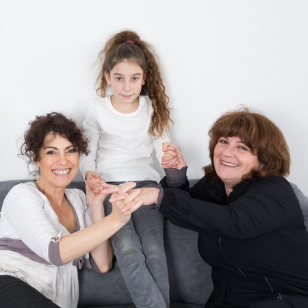 5 10 years old: A cheerful grandmother with her daughter and her granddaughter Indoors Stock Photo