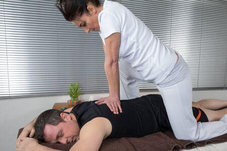 one man: One man and woman performing back shiatsu massage