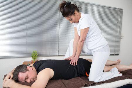 shiatsu: One man and woman performing back shiatsu massage