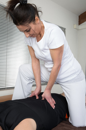 Man and woman performing back shiatsu massage Stock Photo