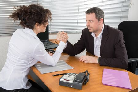 businesspartners: Business couple arm wrestling at the office