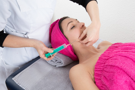 receives: Portrait of beautiful woman receives an injection in her cheek