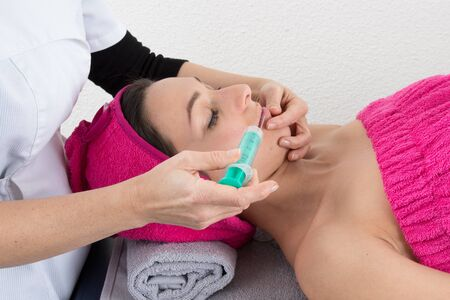 injuring: Cosmetic botox injection in the female face. Lips and cheek zone