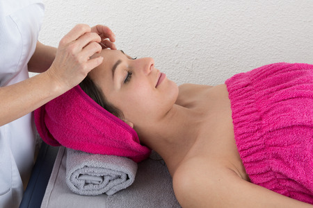 Woman lying on massage table getting acupuncture photo
