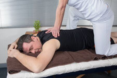 two women and one man: One man and woman performing back shiatsu massage