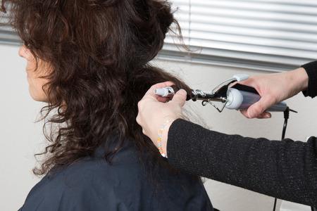 Hairdo with electric hair curler by a hair dresser photo