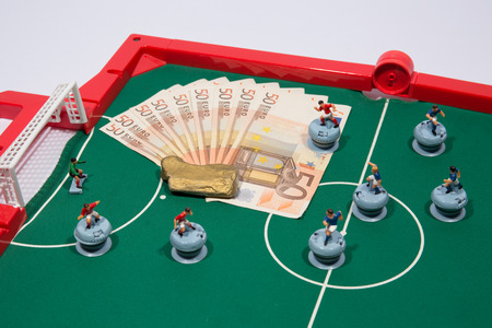 Figures of footbal players on euro banknotes and gold bullion photo