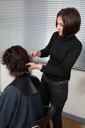 split ends: Stylist cutting split ends on her client at the salon