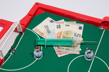 winning bid: Figures of footbal players on euro banknotes,  syringe