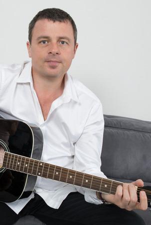 Schließen Sie oben auf einem Mann spielt Gitarre zu Hause