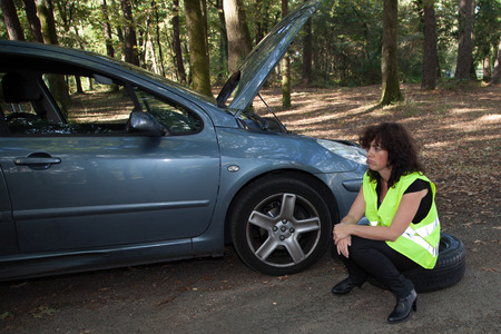 broken down: Female driver waiting next to broken down car