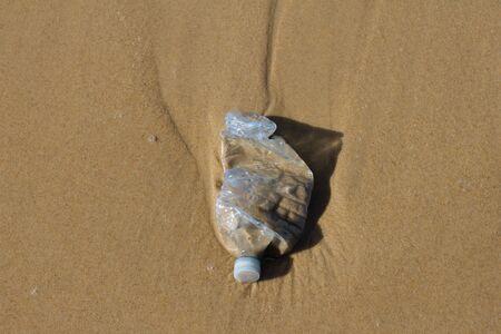 tirar basura: Una botella de pl�stico azul que cubr�an una playa - la contaminaci�n