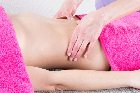Beautiful girl having stomach massage, ayurveda massage