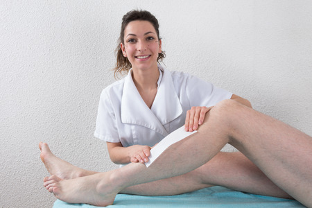 cosmetician: Removing hair from man leg - waxing legs
