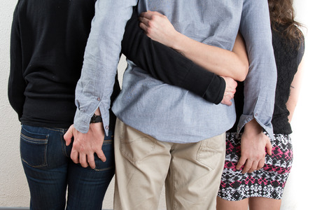 two women and one man: Back view of three people one man and two women looking. Stock Photo