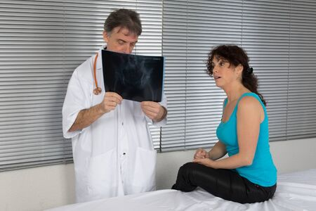 Male doctors pointing at his patient x-ray sheet in clinic photo