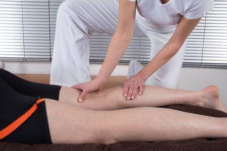 shiatsu: Man and woman performing legs shiatsu massage