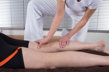Man and woman performing legs shiatsu massage photo