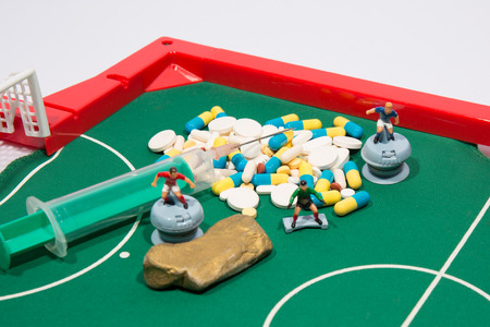 Figures of football players on euro banknotes, syringe and pills