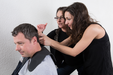 Man at the hairdresser,  drying his hair with a blow dryer photo