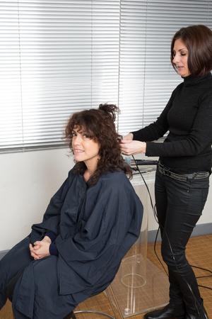 hair curler: Hairdo with electric hair curler by a hair dresser