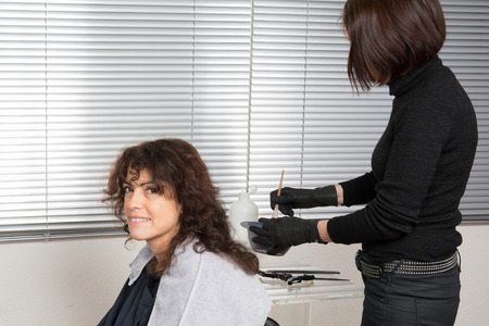 parlor: Woman having her hair dyed by beautician at parlor