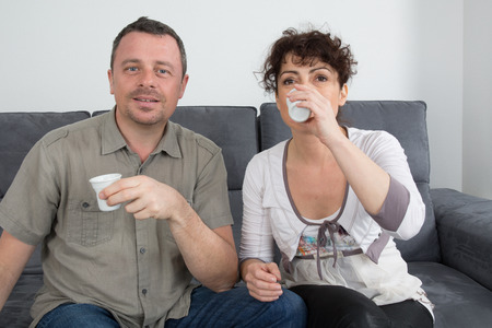 couple on couch: Couple drinking a coffee on a couch