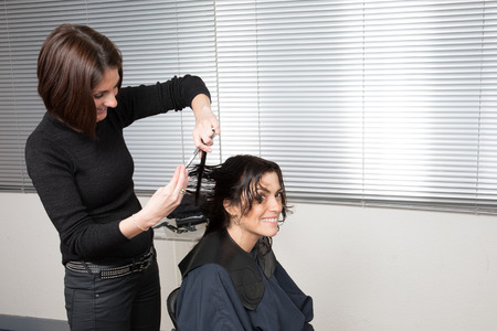 Lady cutting hair at the hairdresser isolated on white background photo