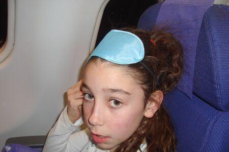 eye mask: Little girl with  sleep eye mask on the plane Stock Photo