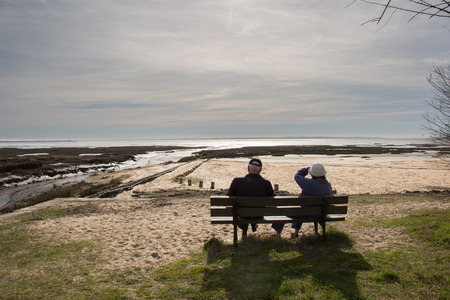 Rear view of a happy romantic senior couple sitting on a park bench Stockfoto