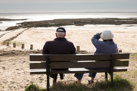 Rear view of a happy romantic senior couple sitting on a park bench photo