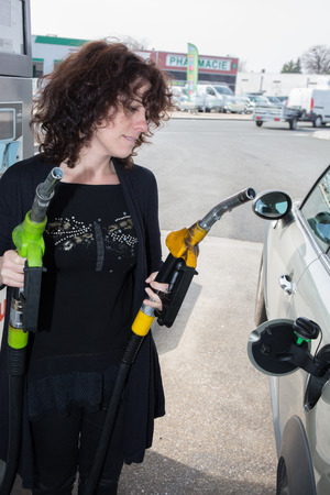refueling: woman refueling her car at the gas station