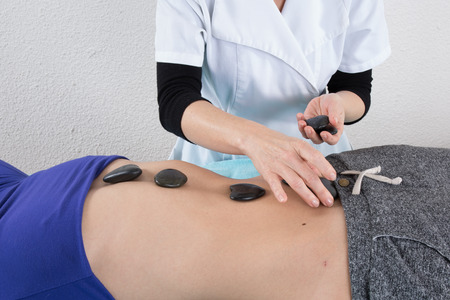 adultery: Adult woman having hot stone massage in spa salon. Beauty treatment concept.