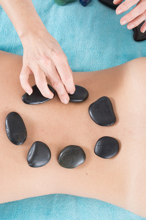 stone massage: Adult woman having hot stone massage in spa salon. Beauty treatment concept.