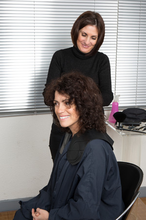 hairdresser parlor: Hairdresser blow drying womans hair after giving a new haircut at parlor Stock Photo