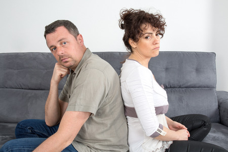 Couple Who-have fallen out over a disagreement sitting on a sofa